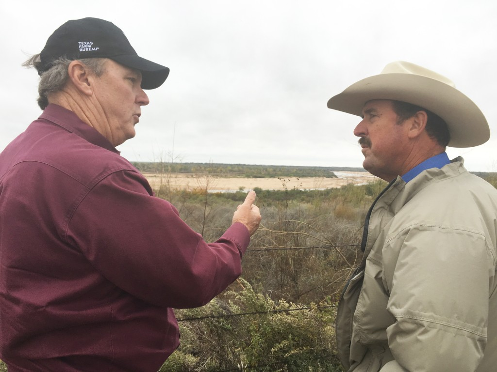 With the Red River in the background, Texas Farm Bureau President Russell W. Boening (right) is briefed on the BLM property issue by Red River landowner Tommy Henderson.